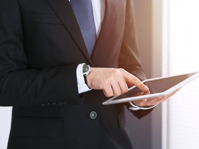 Businessman using digital tablet while standing near window in office, close-up. Copy space area